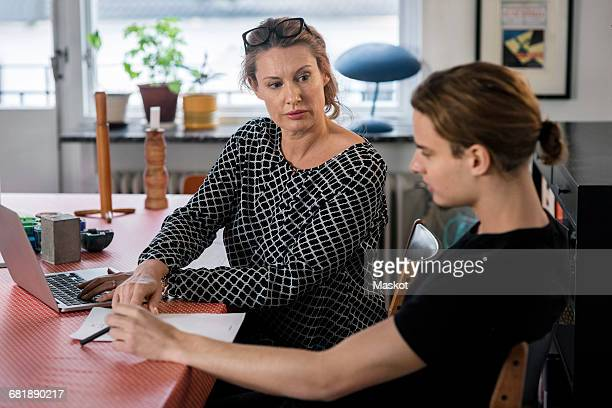 Mother and son using laptop at dining table