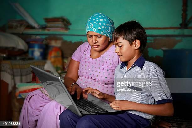 Mère et fils à l'aide d'ordinateur portable à la maison