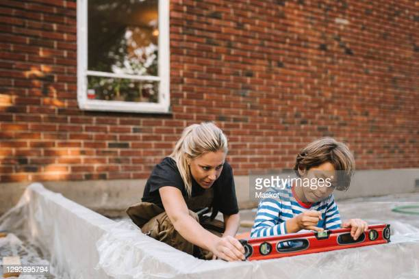 mother and son using level on concrete wall against house during summer - renovation stock pictures, royalty-free photos & images