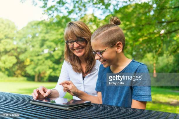 Mother and son using tablet outdoors