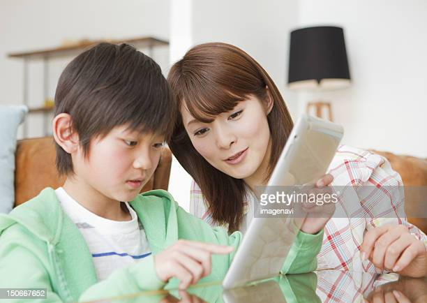 Mother and son using tablet PC