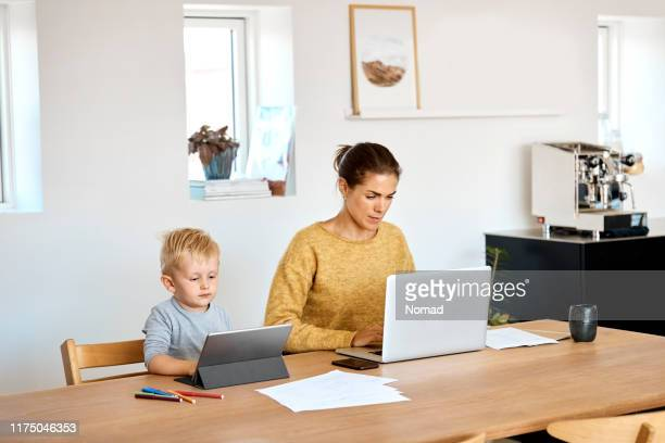 mother and son using technologies at home - home interior stock pictures, royalty-free photos & images