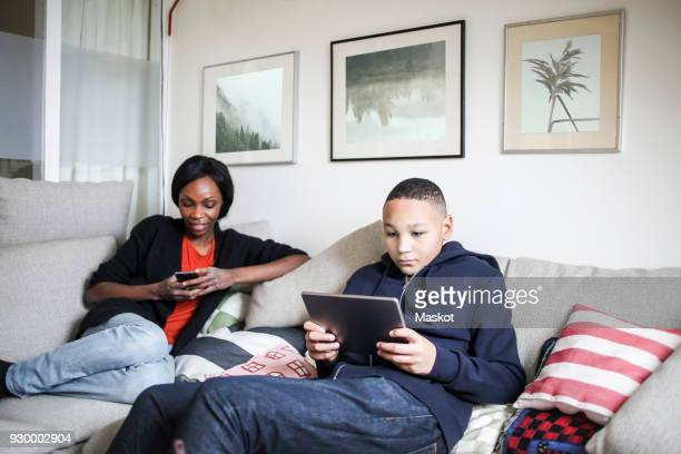 Mother and son using technologies on sofa at home