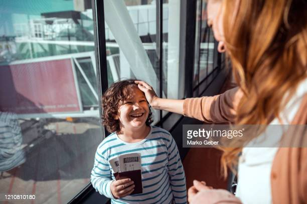 mother and son waiting to board the airplane - kid in airport stock pictures, royalty-free photos & images