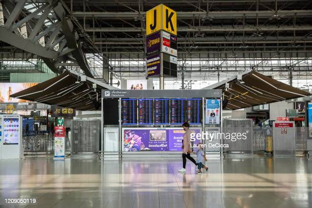 Mother and son walk through an empty Suvarnabhumi Airport after Thailand's government announced that the country would be suspending all...