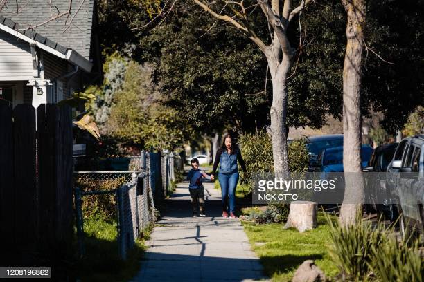 A mother and son walk through one of the neighborhoods of Stockton where participants in the city's universal basic income program live in Stockton...