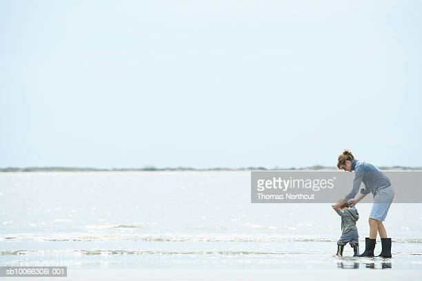 Mother and son (15-18 months) walking along shore, side view
