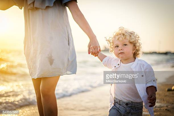 mother and son walking at the beach - mothers day beach stock pictures, royalty-free photos & images