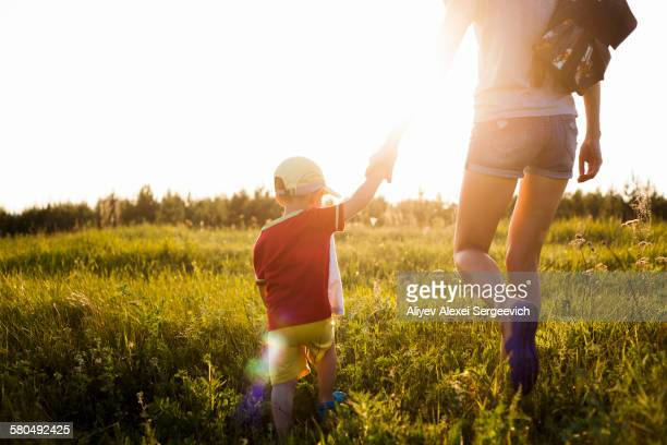 Mother and son walking in rural field
