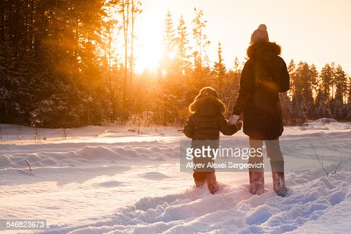 Mother and son walking in snowy forest clearing