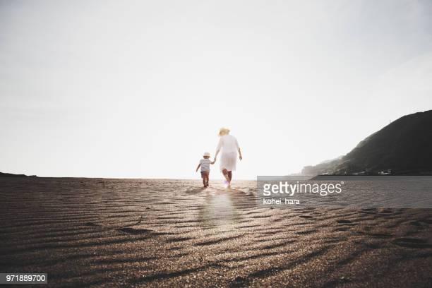 母と息子の浜で歩く - 夏休み ストックフォトと画像