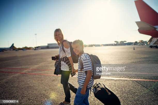 mother and son walking on airstrip - tourist stock pictures, royalty-free photos & images