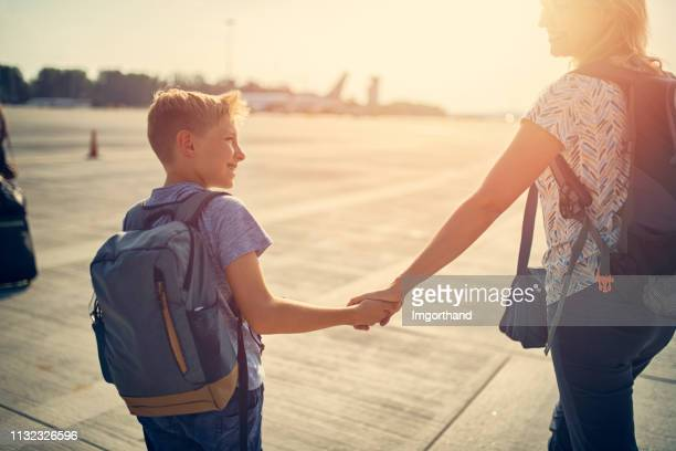 mother and son walking on airstrip - airfield stock pictures, royalty-free photos & images