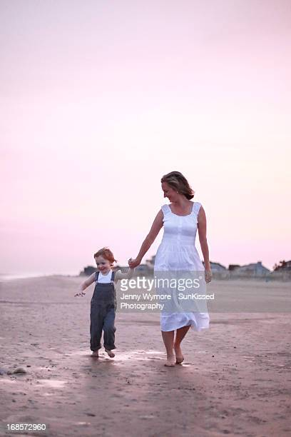 Mother and son walking on beach.