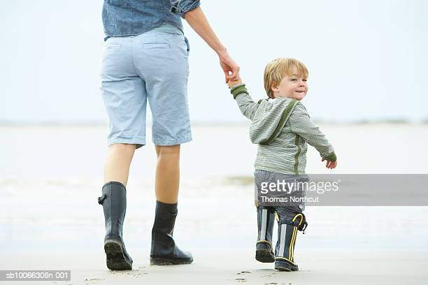 Mother and son (15-18 months) walking on beach, rear view