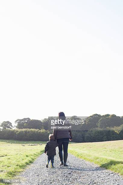 Mother and son walking on dirt road