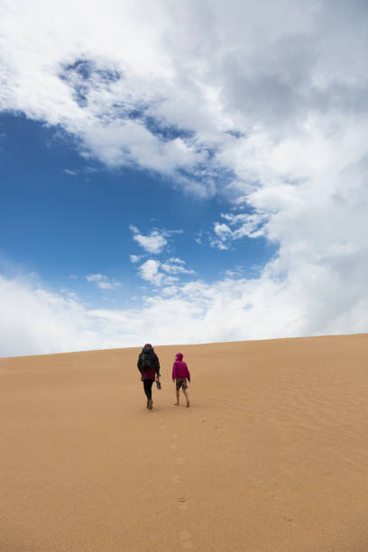 Mother and son walking on sand dune, Wilsons Promontory, Victoria, Australia