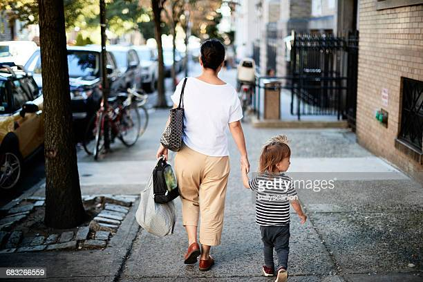 Mother And Son Walking On Street.