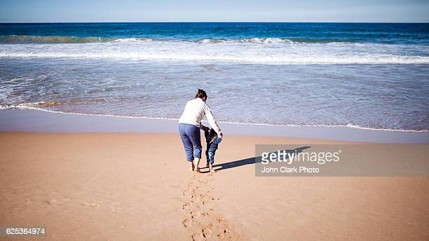mother and son walking on the beach - pacific ocean stock pictures, royalty-free photos & images