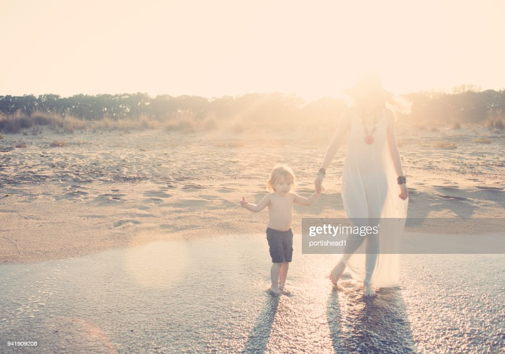 Mother and son walking on the beach : Stock Photo