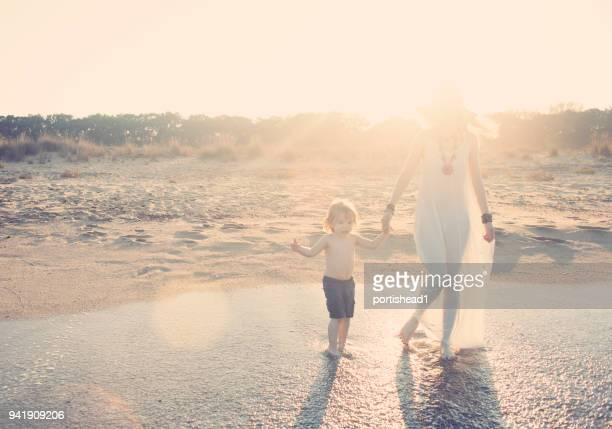 mother and son walking on the beach - overexposed stock pictures, royalty-free photos & images