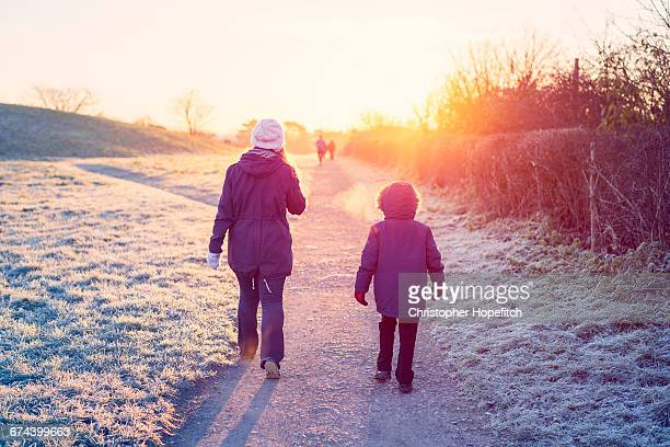 Mother and son walking through a park in winter