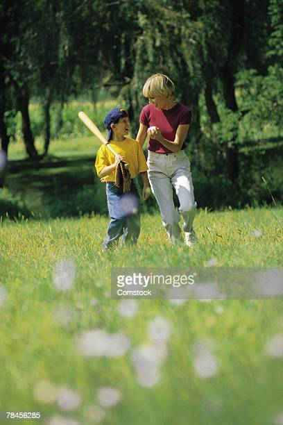 mother and son walking through park with baseball gear - baseball mom stock pictures, royalty-free photos & images
