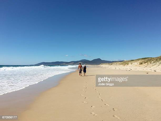 Mother and son walking together on secluded beach