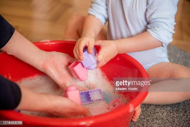 jouets de lavage et de nettoyage de mère et de fils dans un bol de lavage dans un salon - cuvette photos et images de collection