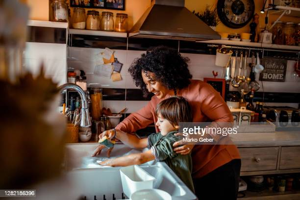 mother and son washing dishes - lifestyle stock pictures, royalty-free photos & images