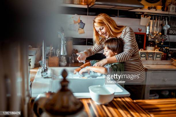 mother and son washing dishes - washing stock pictures, royalty-free photos & images