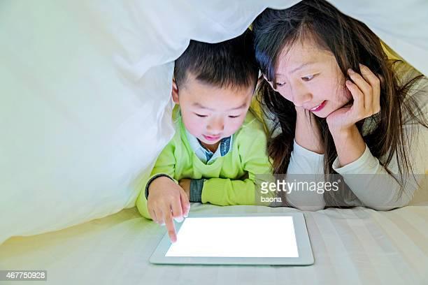 Mutter und Sohn bei digitalen tablet im Bett