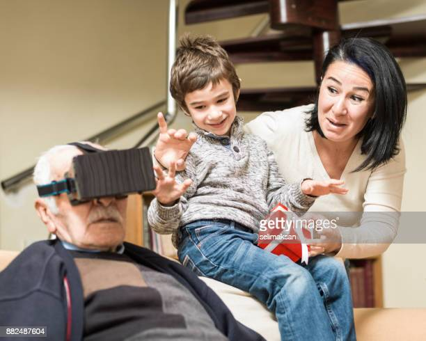 Mother And Son Watching Grandfather Experiencing VR Technology