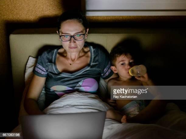 mother and son watching laptop - diaper boy stock-fotos und bilder