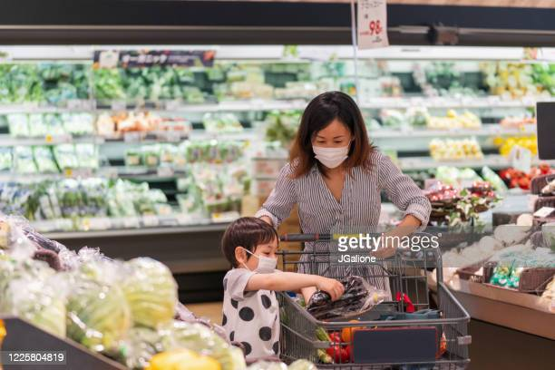 mother and son wearing face masks shopping together in a supermarket - asia stock pictures, royalty-free photos & images