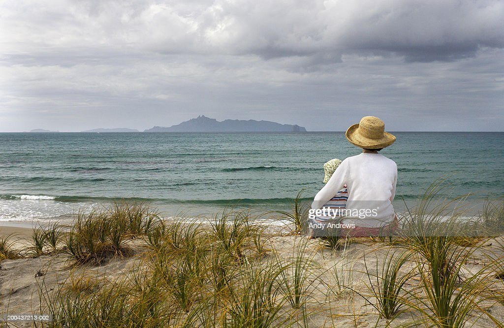 Mother and son (2-4) wearing sun hats sitting on beach, rear view. : Stock Photo