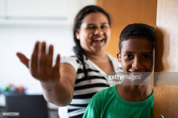 Mother and son welcoming and opening door