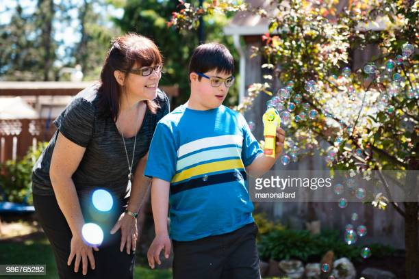 Mother and son with autistic and down syndrome son in daily lives