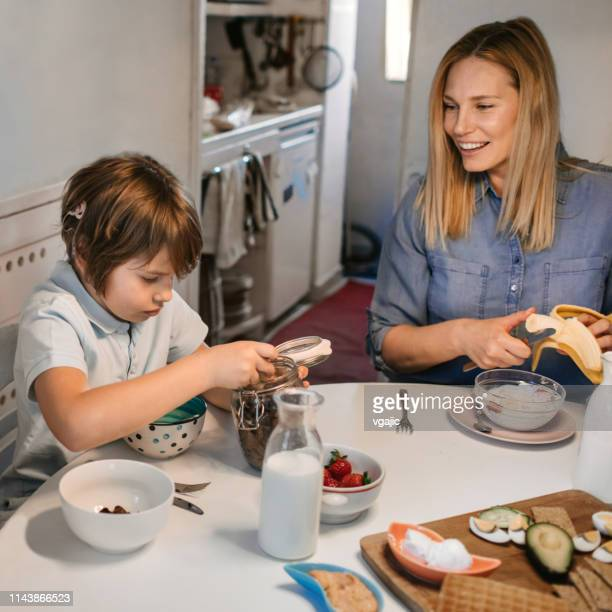 mother and son with cochlear implant having healthy breakfast - cochlear implant stock pictures, royalty-free photos & images