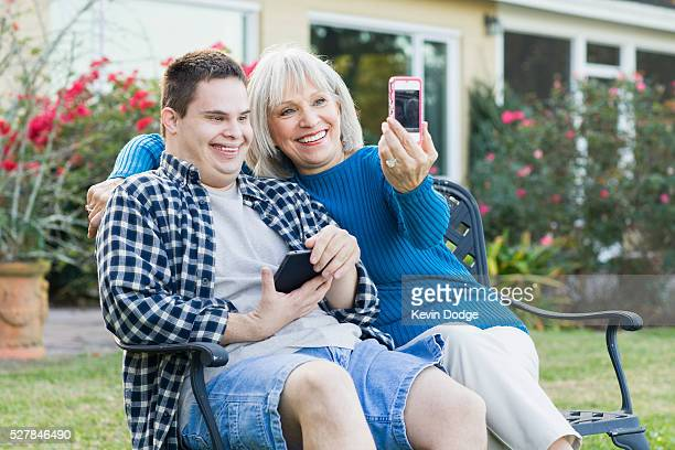 Mother and son (16-17) with Down Syndrome taking pictures with smart phone