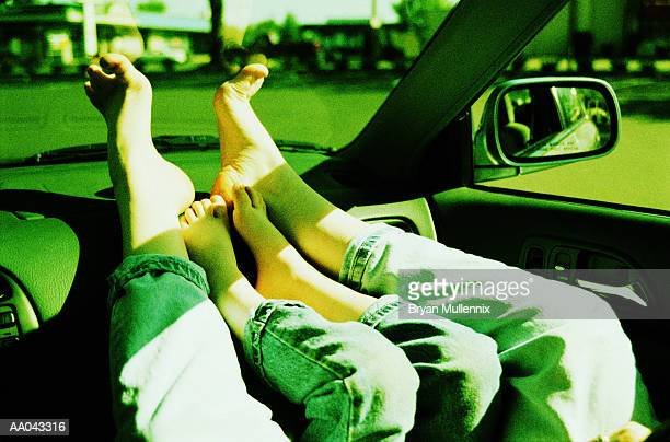 Mother and son with feet on dashboard, low section