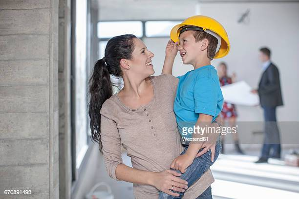 Mother and son with hard hat on construction site