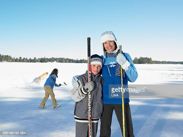 mother and son (9-11) with hockey sticks, portrait, girl in background - ice hockey glove stock pictures, royalty-free photos & images