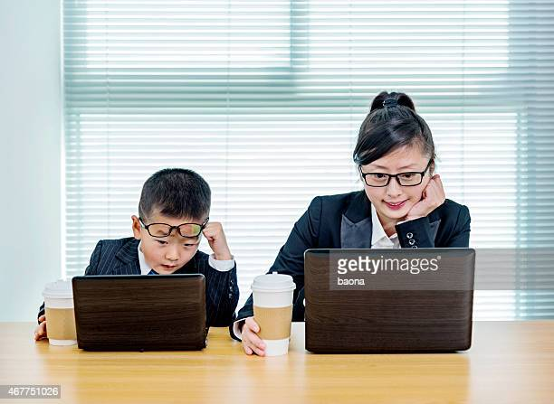Mother and son with matching glasses, coffee and laptop