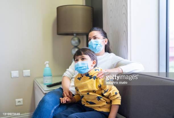 mutter und sohn mit schützender gesichtsmaske schauen im krankenzimmer vor dem fernseher. - film and television screening stock-fotos und bilder