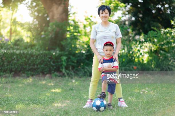 mother and son with soccer ball posing for camera - japan women football stock photos and pictures
