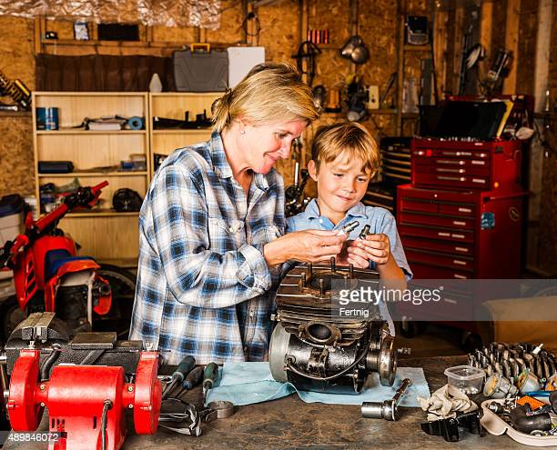 Mother and son working on motorcycle engine in their garage
