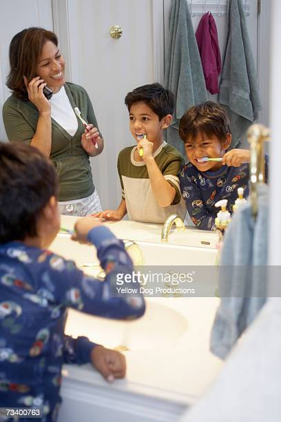 Mother and sons (6-8) brushing teeth, woman using cell phone
