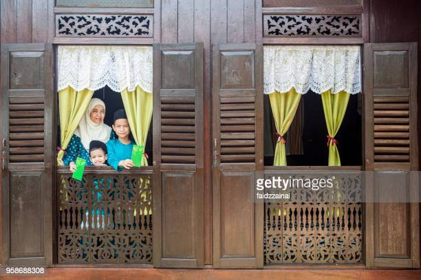 mother and sons celebrates on eid-ul-fitr/ aidilfitri / hari raya - hari raya stock pictures, royalty-free photos & images