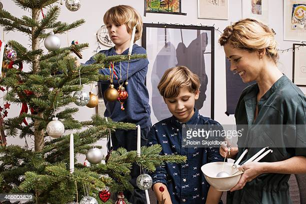 Mother and sons decorating X mas tree